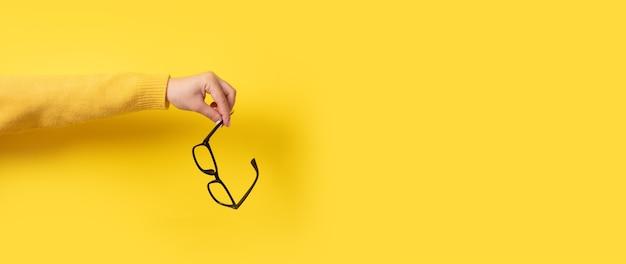 Okulary do widzenia w ręku na żółtym tle, obraz panoramiczny