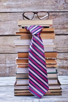 Okulary i krawat. książki na drewnianej półce. biznesowy styl życia mężczyzn.