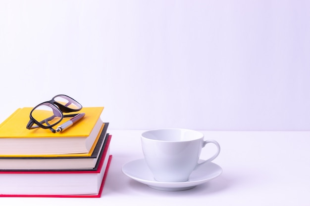 Okulary i książki na białym stole