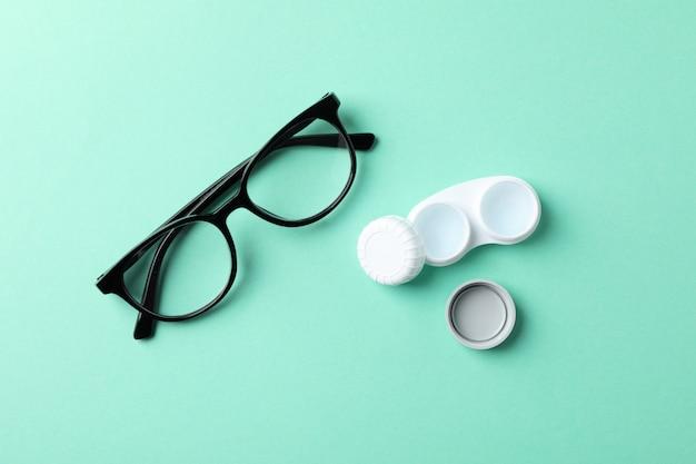 Okulary i soczewki kontaktowe na stole mięty, widok z góry