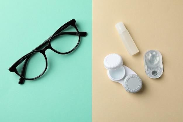 Okulary i soczewki kontaktowe na stole w dwóch odcieniach, widok z góry