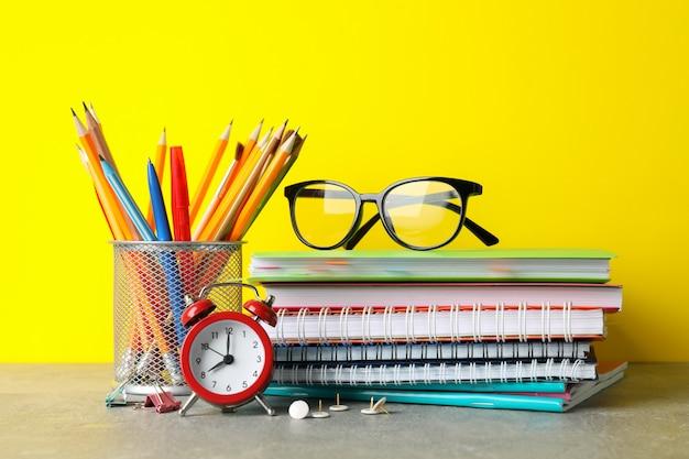Okulary i stacjonarne na szarym stole. koncepcja nauki