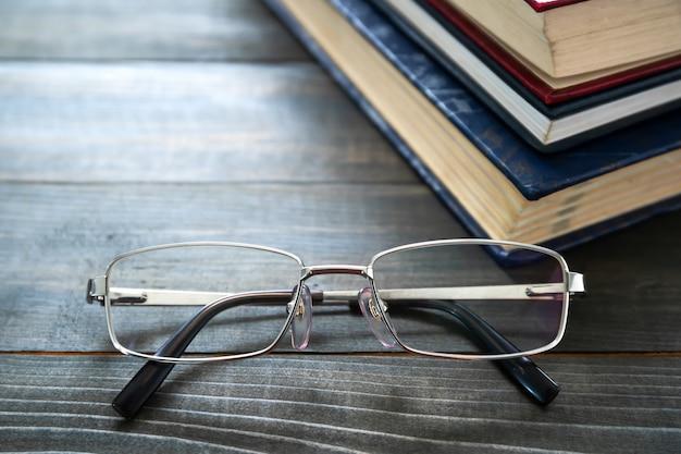 Okulary i stos książek w twardej oprawie na drewnianym stole