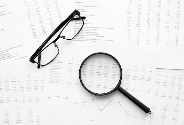Okulary i szkło powiększające na danych finansowych. koncepcja badań biznesowych i finansowych.
