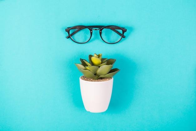 Okulary i sztuczna roślina w białym garnku na niebieskim tle