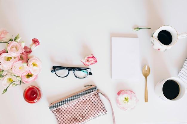 Okulary i torebka w pobliżu filiżanek