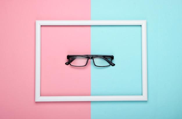 Okulary korekcyjne w białej oprawie na różowo-niebieskiej pastelowej powierzchni