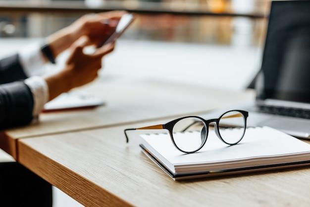 Okulary na biurku w pobliżu laptopa i notatnika