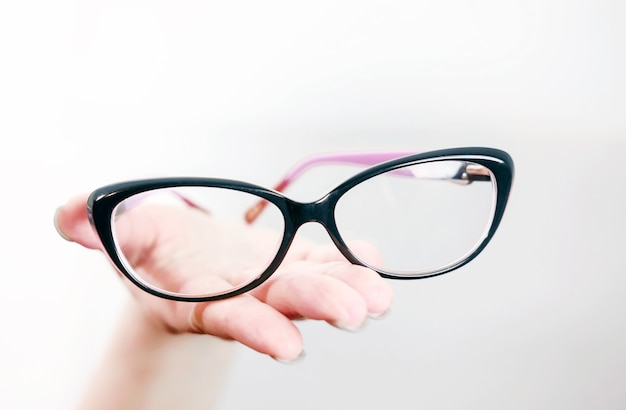 Okulary na kobiecej dłoni, okulary na kobiecej dłoni, wyciągnięte ręce w okularach, leżą na dłoniach