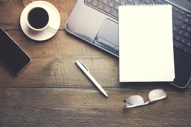 Okulary na komputerze, filiżanka kawy i papier na drewnianym stole