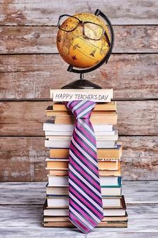 Okulary na kuli ziemskiej i krawacie. stos książek i karty. gratuluję nauczycielowi geografii.