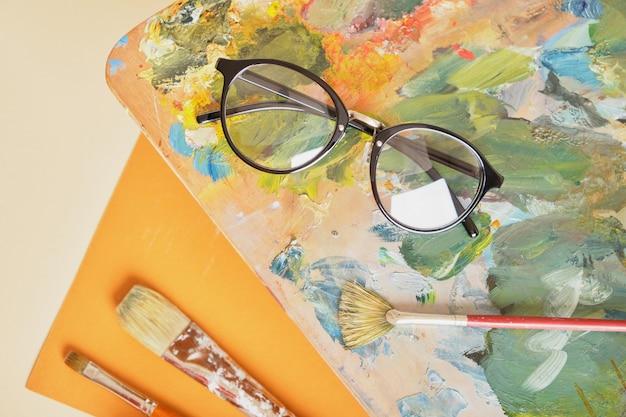 Okulary na palecie z farbami brązowe tło, koncepcja warsztatu artysty widok z góry