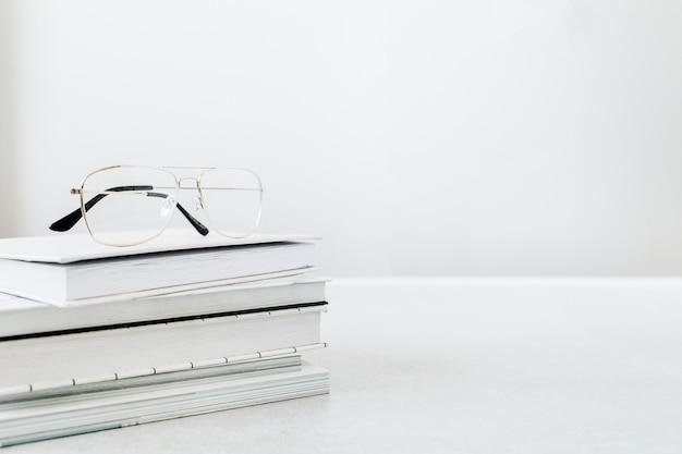 Okulary na stosie książek. minimalna koncepcja nagłówka bohatera edukacji.