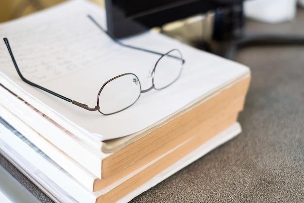 Okulary na stosie książki z komputerem na stole
