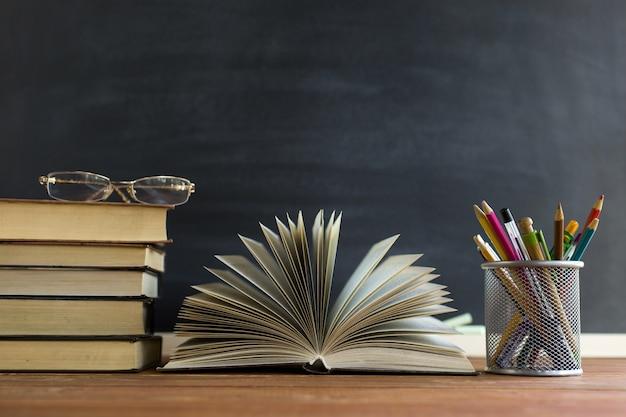 Okulary nauczyciel książki i stojak z ołówkami na stole, na tle blackboard z kredą
