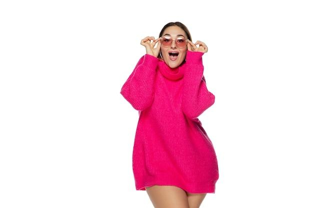 Okulary. piękna młoda kobieta jasny różowy wygodny sweter, długi rękaw na białym tle na tle białego studia. styl magazynu, moda, koncepcja piękna. modne pozowanie. miejsce na reklamę.
