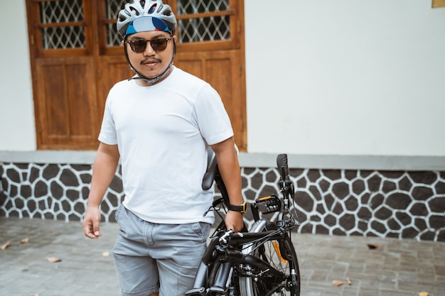 Okulary przeciwsłoneczne dla azjatyckich mężczyzn trzymające składany rower, aby przygotować się do pracy