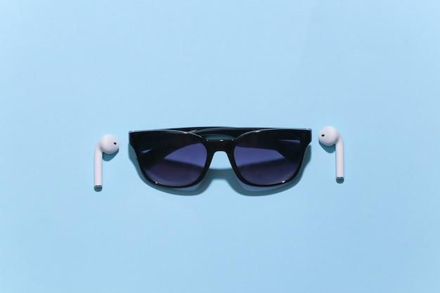 Okulary przeciwsłoneczne i białe prawdziwe bezprzewodowe słuchawki bluetooth na jasnym niebieskim tle.