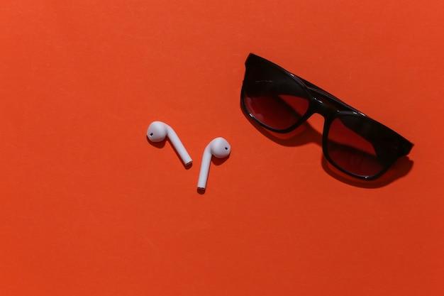 Okulary przeciwsłoneczne i białe prawdziwe bezprzewodowe słuchawki bluetooth