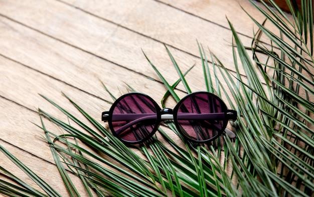 Okulary przeciwsłoneczne i gałąź palmy na podłoże drewniane
