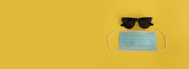 Okulary przeciwsłoneczne i maska medyczna na żółtym tle. wolne miejsce na tekst, miejsce na kopię. tło wakacje. podróżuj w czasie covid-19. wakacje, wakacje, lot w czasach korony.