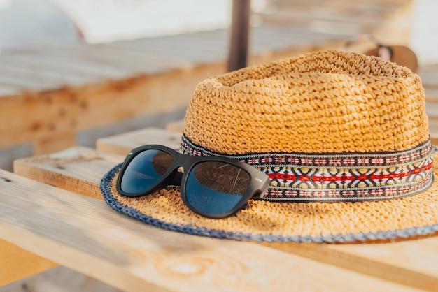 Okulary przeciwsłoneczne leżą na kapeluszu na leżaku na plaży