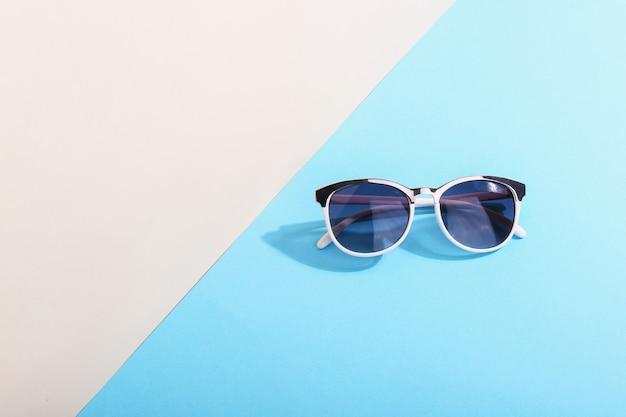 Okulary przeciwsłoneczne leżą na kolorowych rzucających ostry cień, koncepcyjne lato i relaks, minimalizm.