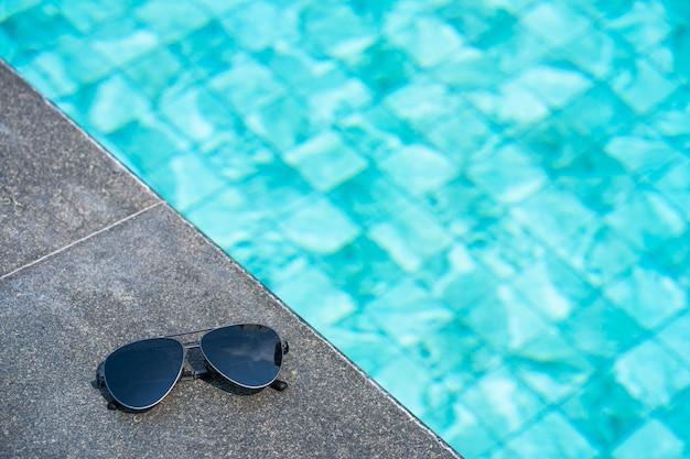 Okulary przeciwsłoneczne na brzegu basenu. koncepcja wakacji z bliska