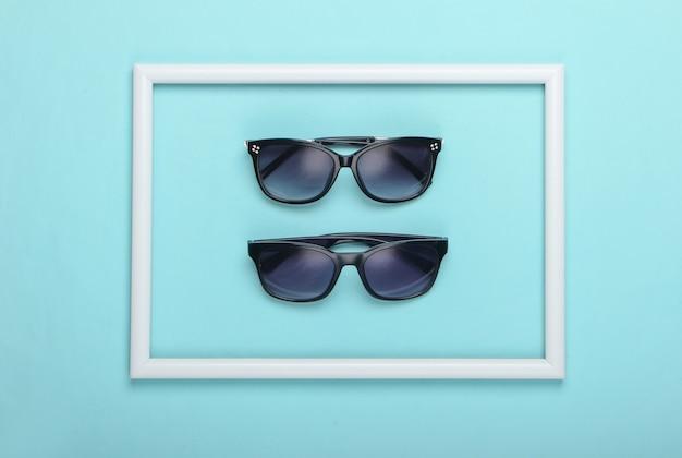 Okulary przeciwsłoneczne na niebieskiej powierzchni z białą oprawką