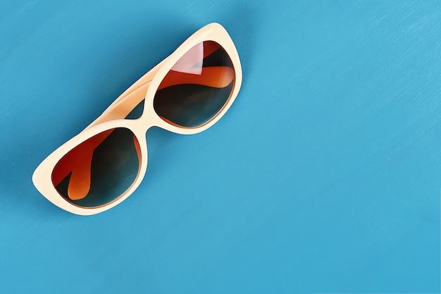 Okulary przeciwsłoneczne na niebieskim tle. widok z góry. tło lato.