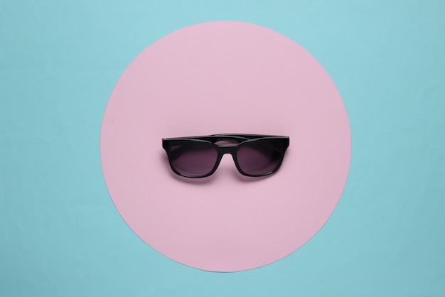 Okulary przeciwsłoneczne na niebieskim tle z różowym pastelowym kołem. widok z góry