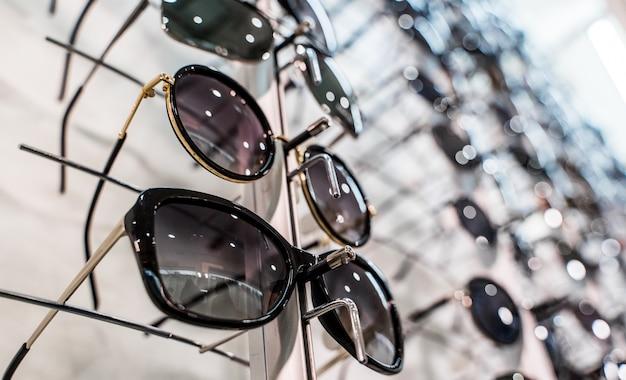 Okulary przeciwsłoneczne na półkach sklepowych. stojak z okularami w sklepie z optyką. stojak sprzedaży okularów przeciwsłonecznych. na sprzedaż kolorowy wyświetlacz okularów przeciwsłonecznych. zbliżenie.