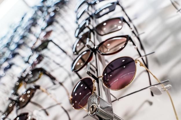 Okulary przeciwsłoneczne na półkach sklepowych. stojak z okularami w sklepie z optyką