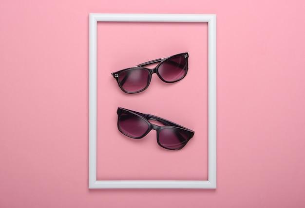 Okulary przeciwsłoneczne na różowej powierzchni z białą oprawką