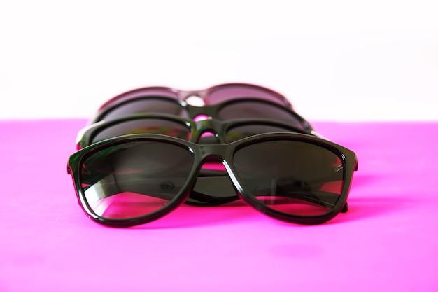 Okulary przeciwsłoneczne na różowym pastelowym tle. okulary z czarnymi oprawkami. akcesoria modowe do ochrony oczu przed promieniowaniem uv.