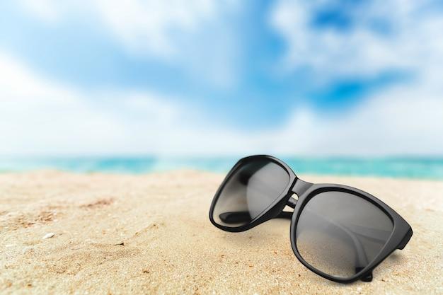 Okulary przeciwsłoneczne na tle piaszczystej plaży