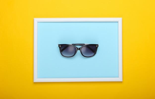 Okulary przeciwsłoneczne na żółtej powierzchni z ramką na zdjęcie