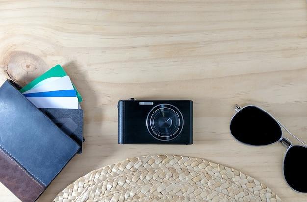 Okulary przeciwsłoneczne, skórzany portfel, aparaty fotograficzne, karta kredytowa, czapka na drewnianej podłodze