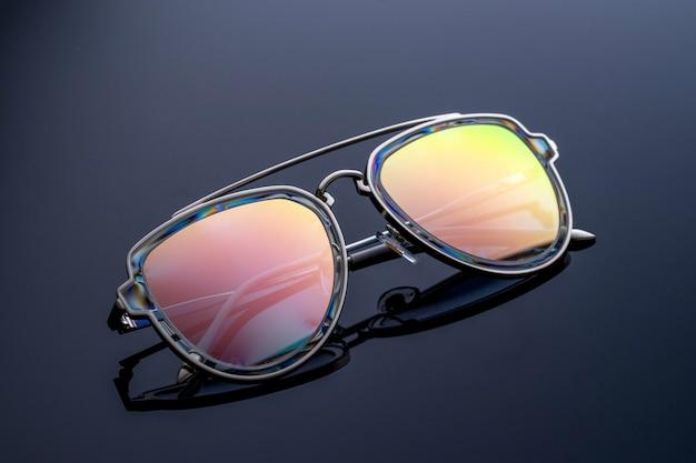 Okulary przeciwsłoneczne w kolorze kameleona, mienią się w słońcu.