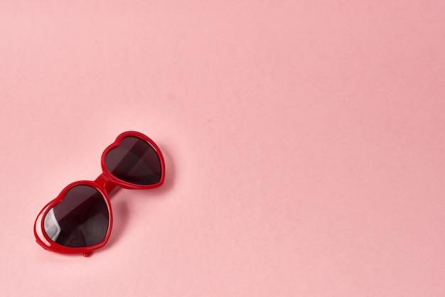 Okulary przeciwsłoneczne w kształcie serca z czerwonymi oprawkami na różowej powierzchni
