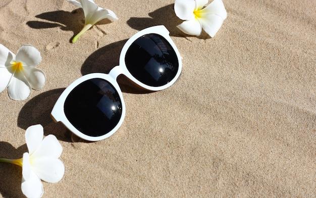 Okulary przeciwsłoneczne z białym kwiatem plumeria na piasku. lato w tle