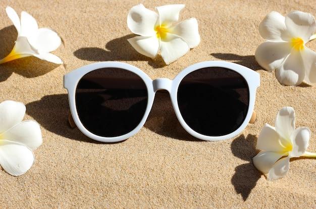 Okulary przeciwsłoneczne z białym kwiatem plumeria na piasku.
