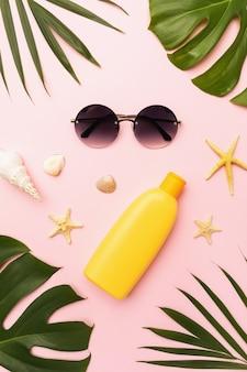 Okulary przeciwsłoneczne z filtrem przeciwsłonecznym muszle chico i liście monstera na różowym tle