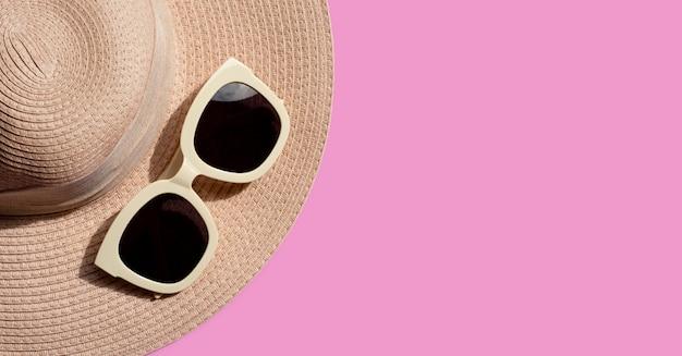 Okulary przeciwsłoneczne z letnim kapeluszem na różowym tle. ciesz się wakacyjną koncepcją.