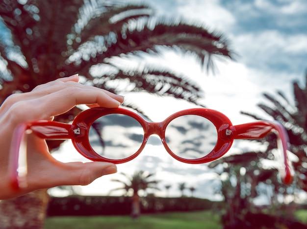 Okulary przeciwsłoneczne z palmami. koncepcja wakacje. dziewczyna trzyma w ręce modne czerwone okulary i przygotowuje się do ich noszenia.