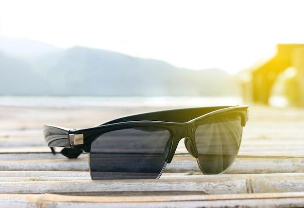 Okulary przeciwsłoneczne z selektywnym skupieniem na bambusowej podłodze z rozbłyskowym światłem wschodu słońca, marzeniem miękkim stylem