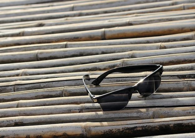 Okulary przeciwsłoneczne z selektywnym skupieniem na bambusowej podłodze