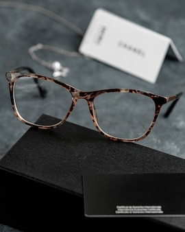 Okulary przeciwsłoneczne z widokiem z przodu na szarym biurku ze srebrnymi bransoletkami odizolowały wzrok