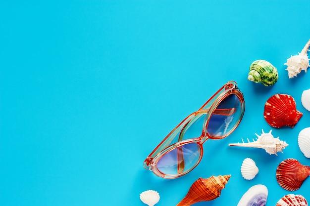 Okulary przeciwsłoneczni i morze skorupy na błękitnym tle dla podróży akcesoriów i relaksu pojęcia