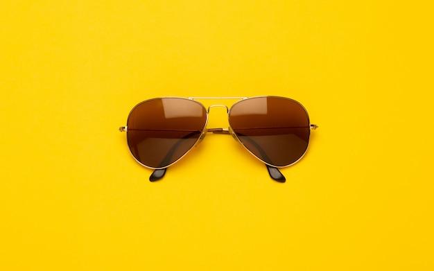 Okulary przeciwsłoneczni odizolowywający na kolorze żółtym